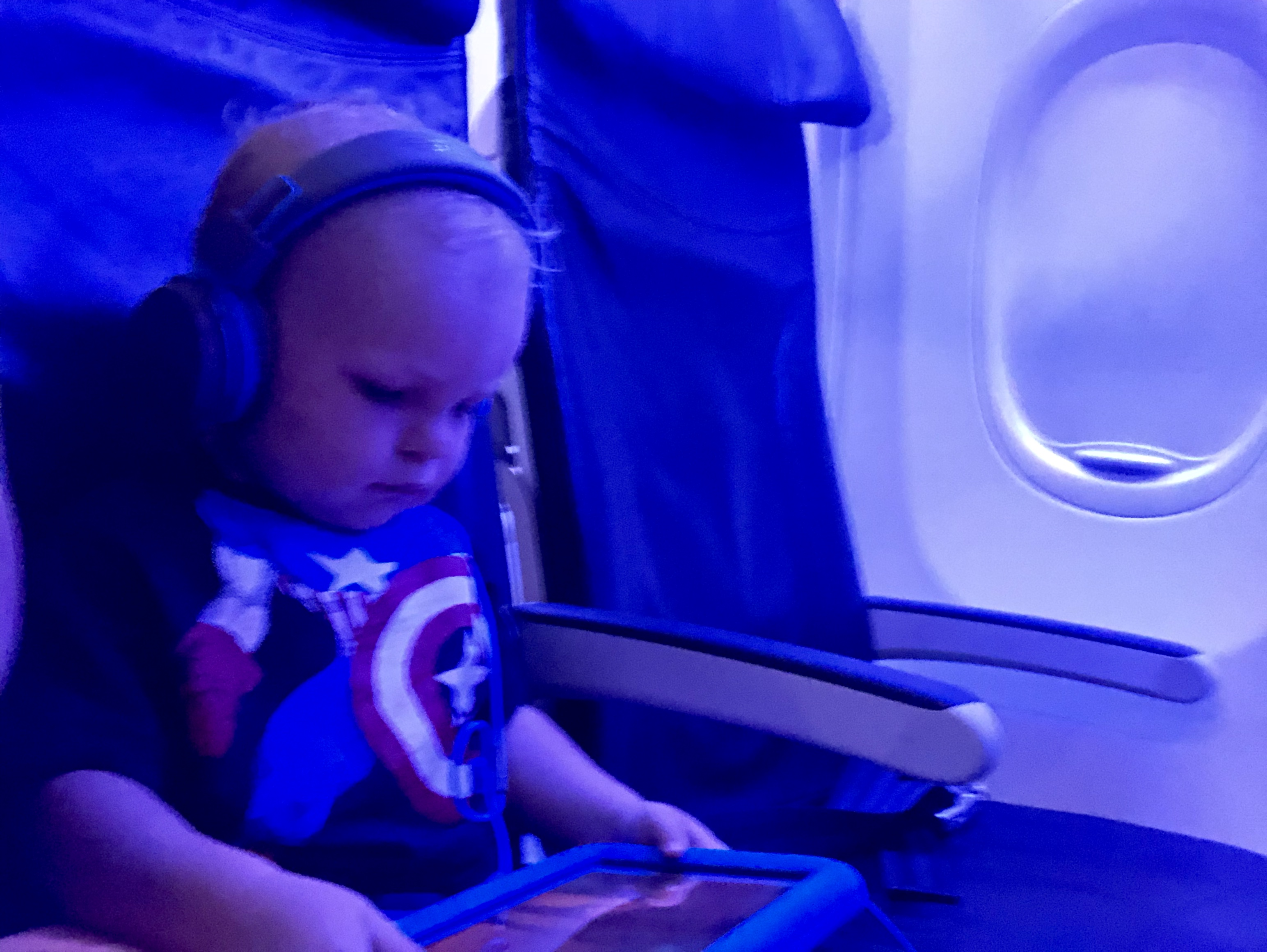 Toddler on an airplane with headphones and a tablet. Traveling with toddlers. Tips.
